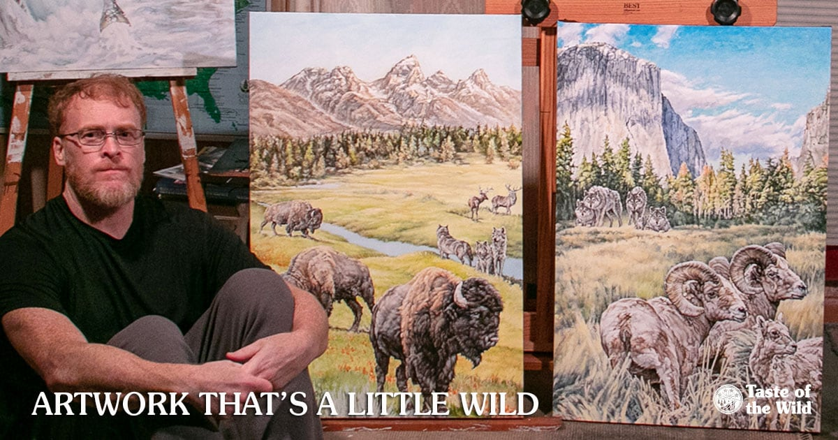 Painter Kevin Ritchie Next to Two Paintings Used on the Product Bags | Taste of the Wild Pet Food